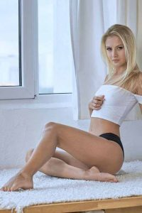 Adelle sitting on rug in black panties, white top, with hand below breasts