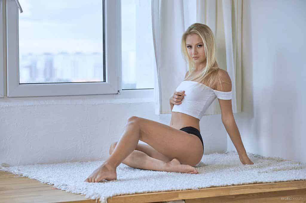 Adelle sitting on rug in black panties, white top, with hand below breasts.