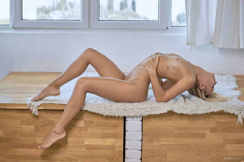 Adelle laying on table fully nude.