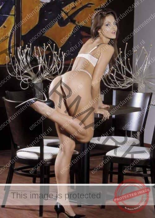 Hazel standing against table in white lingerie.