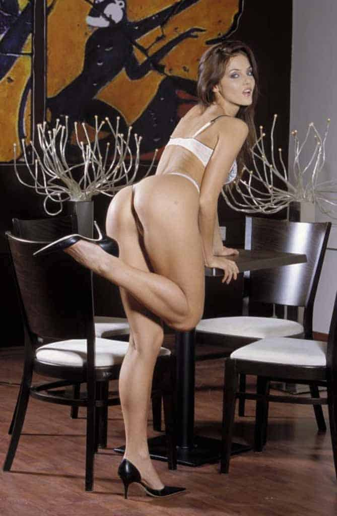 Hazel standing against table in white lingerie.