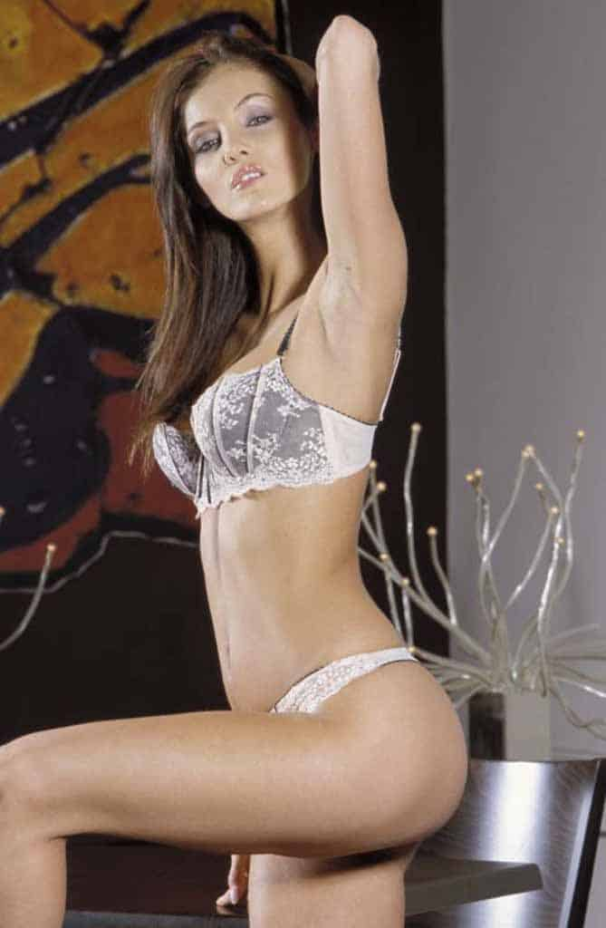 Hazel kneeling one knee on chair in white lingerie.