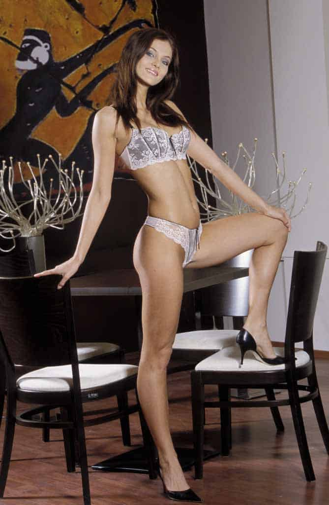 Hazel standing with one foot on chair in white lingerie.