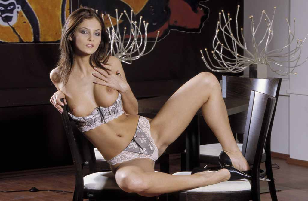 Hazel laying on two chairs with legs spread in white lingerie.