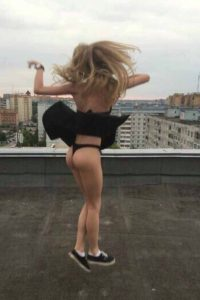 Kayley jumping up with black skirt flying up showing her black panties.