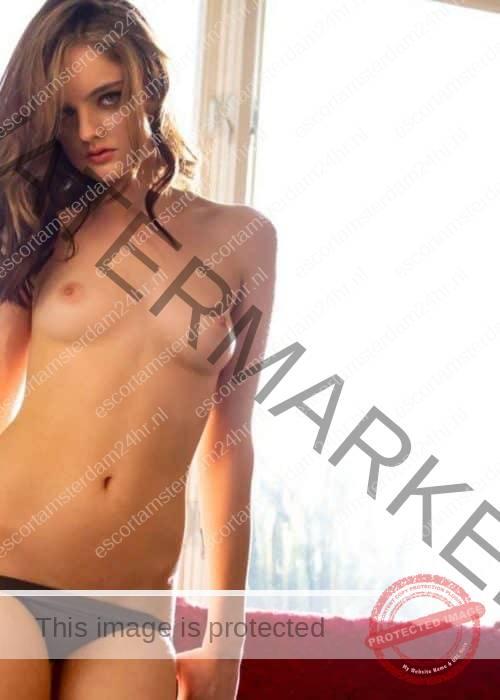 Noelle standing topless pulling down black panties.